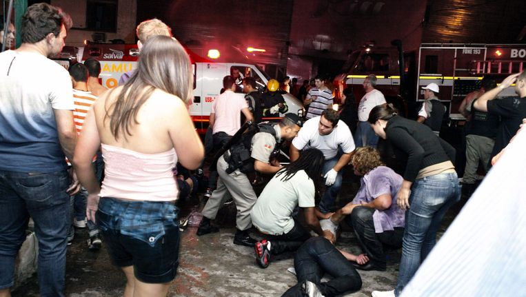 Reddingswerkers helpen een slachtoffer van de brand. Beeld EPA