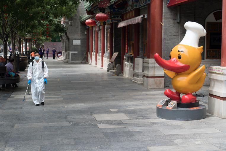Een verlaten straat in de normaal toeristische buurt Dashilan. Dit is de ingang van het bekende maar uitgestorven Beijing Duck restaurant. Beeld Ruben Lundgren