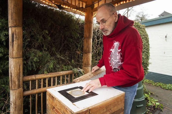 """Dagelijks controleert  Wim Broekman de twee kasten in zijn van bamboe gebouwde bijenstal. """"Kijk, deze zijn heel actief."""""""