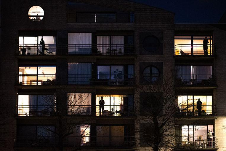 Appartementsbewoners in Gent applaudisseren om 20 uur voor de zorgsector. Beeld Wouter Maeckelberghe
