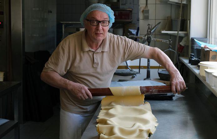 Joseph rolt het deeg uit over de taartvormen.