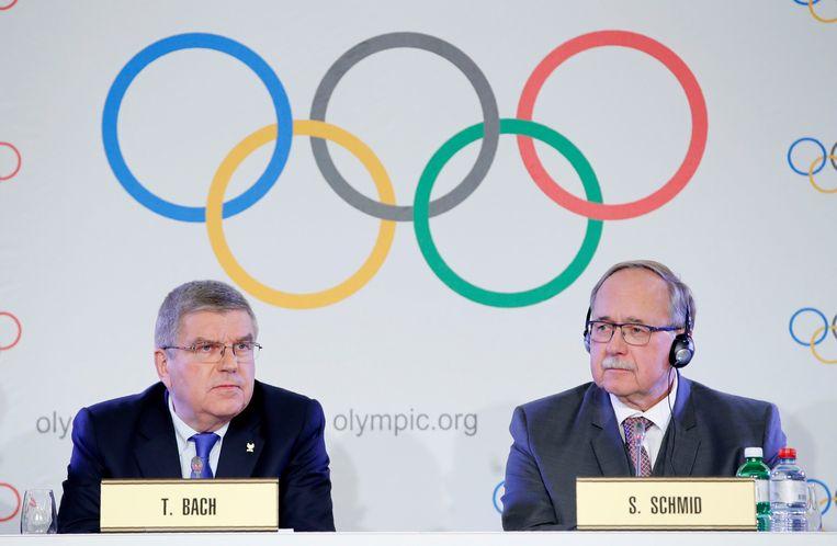 Samuel Schmid, voorzitter van de disciplinaire commissie van het IOC (rechts), en IOC-voorzitter Thomas Bach tijdens de persconferentie in het Zwitserse Lausanne. Beeld Photo News
