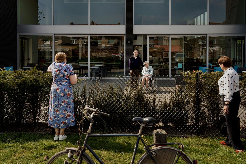 Familie bezoekt de bewoners op afstand in zorgcentrum Westervier in Brugge.  Beeld Eric de Mildt