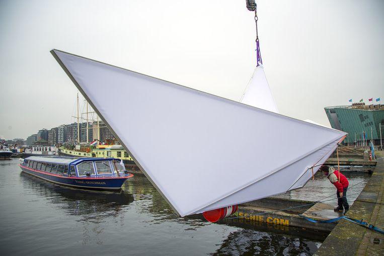 De origamiboot tijdens het ter water laten. Beeld Cris Toala Olivares