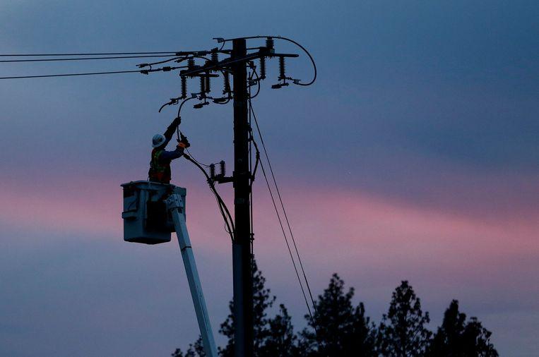 Een werknemer van Pacific Gas & Electric repareert een elektriciteitsleiding in Paradise, het stadje dat vorig jaar vrijwel werd verwoest bij een enorme bosbrand.  Beeld AP
