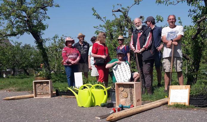 Vrijwilligers van Hof van Seghwaert hangen een lint van bijenhotels op langs een wandelroute tussen de twee buurttuinen.