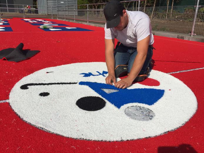 Marijn Dupont van European Hockey Group is bezig met de aanleg van het logo van Hockey Club Berkel Enschot in het nieuwe 'skill'-veldje