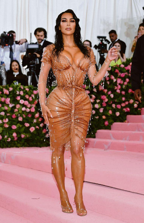 Kim Kardashian in de wetlook-robe die zo strak zat, dat ze rechtopstaand in een verhoogde SUV naar het Met Ball moest. Beeld rv