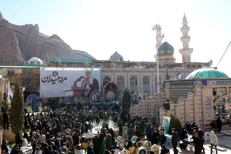 Bezoekers van het graf van de vorig jaar gedode Iraanse generaal Qassem Soleimani (op de poster) in Kerman, Iran. Beeld VIA REUTERS