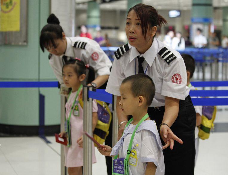 Douanepersoneel helpt de scholieren bij de grensovergang tussen Shenzhen en Hongkong. Beeld reuters