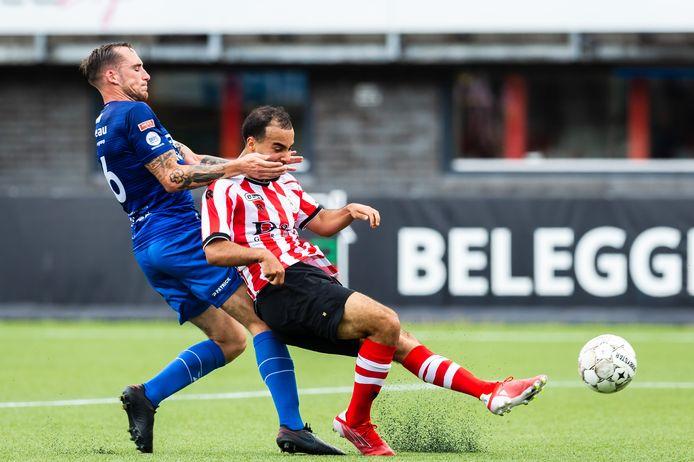 De Treffers-aanvoerder Ricardo Ippel komt handen en voeten tekort om Mohammed Tahiri van Jong Sparta te stoppen.