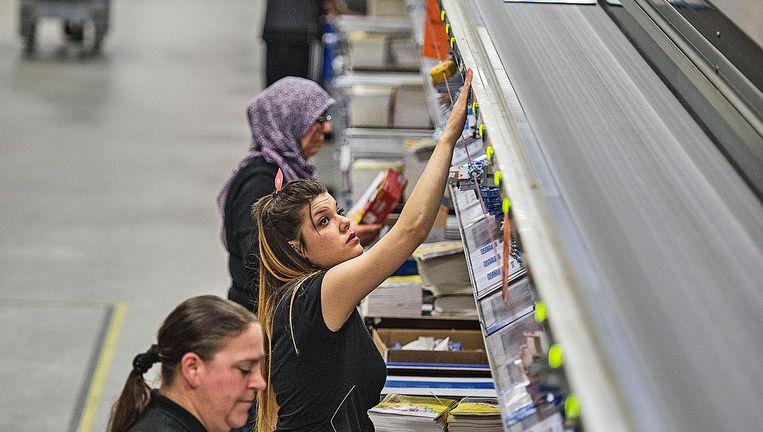 Medewerkers aan de lopende band van het distributiecentrum. Beeld Guus Dubbelman / de Volkskrant