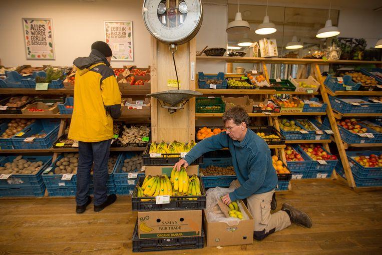 Mede-eigenaar Maarten Rijninks aan het werk in supermarkt De Aanzet in Amsterdam Beeld Maartje Geels