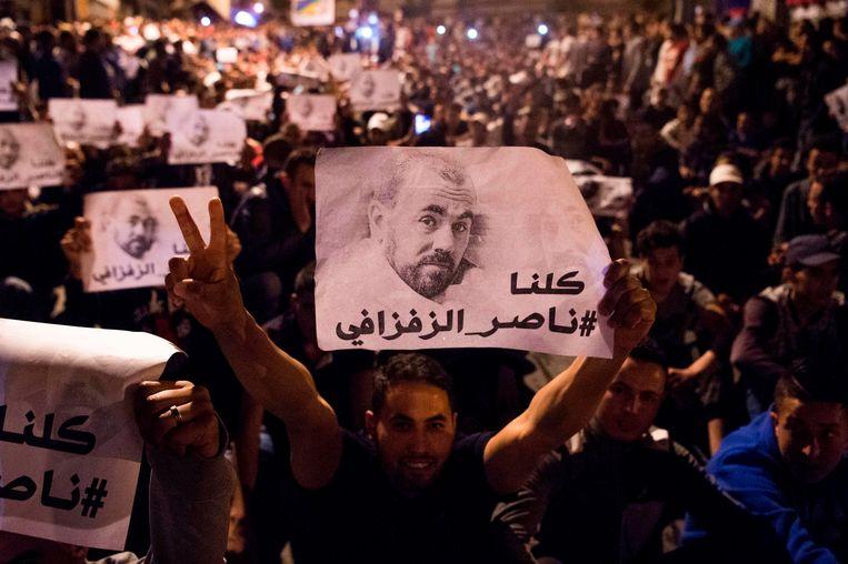 Met een foto van de gearresteerde protestleider Nasser Zafzafi klagen manifestanten in de Marokkaanse Rif-regio de discriminatie, het geweld en de corruptie van de centrale overheid aan. Beeld AFP