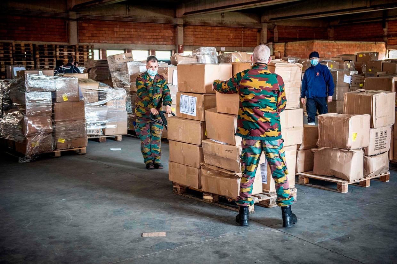 Militairen in Peutie verdelen een lading van 6 miljoen mondmaskers die op 23 maart arriveerde in ons land. Beeld AFP