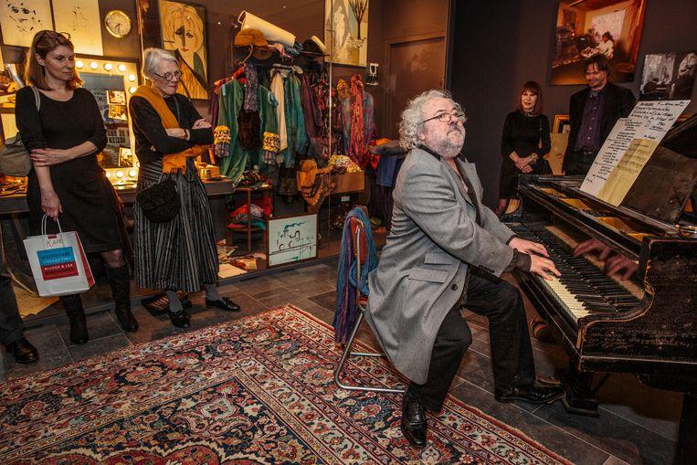 Nico van der Linden geeft een Shaffy-imitatie op de piano van Ramses Shaffy. Op de achtergrond staan Liesbeth List en Shaffy-biograaf Sylvester Hoogmoed.  Beeld Dingena Mol