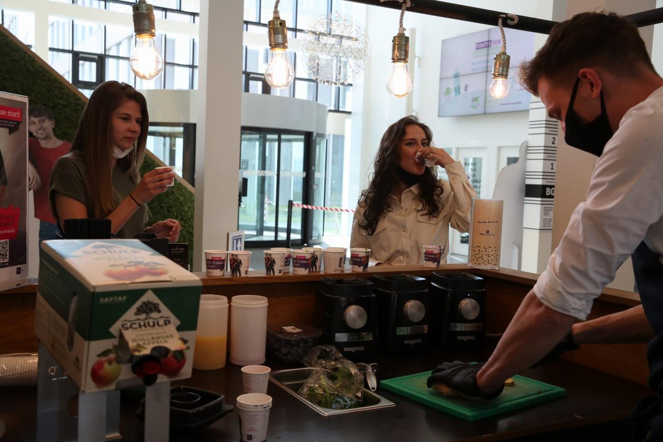 Tweedejaars studenten Lara Coumans (links) en Lisanne Drinhuyzen drinken een smoothie in de hal van de Fontys-opleidingen economie en communicatie.