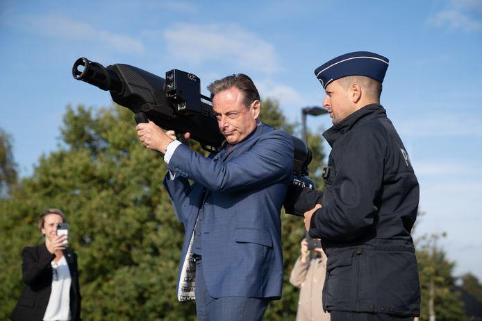 Burgemeester Bart de Wever maakt gebruik van de anti-drone launcher tijdens een demonstratie.