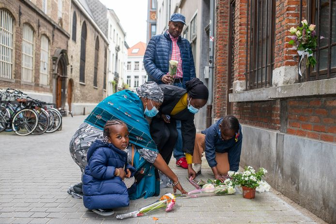 De familie van Oulematou N'Doye legt bloemen neer in de Zwartzusterstraat. Op de voorgrond de kleine Kadia (3) die zo oud is als Luna toen ze werd doodgeschoten.