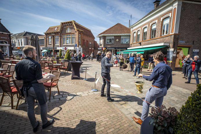 Pastoor Casper Pikkemaat (midden) heropent het terras van restaurant 't Oale Roadhoes van eigenaar Ruud Droste (rechts) in Tubbergen. Kort daarna mogen de mensen die hebben gereserveerd het terras betreden.