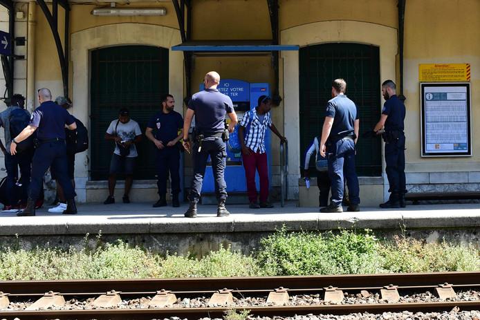 De Franse grenspolitie controleert migranten die de grens met Italië overgegaan zijn in het treinstation van Menton.