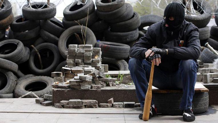 Een demonstrant zit nabij het gebouw van de regionale regering in Donetsk. Beeld REUTERS