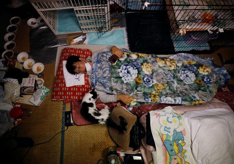 Sakae Kato bleef achter na de nucleaire ramp in Fukushima, om de aan hun lot overgelaten katten te verzorgen. Hij slaapt op een futon op de grond, omringd door dieren en voederbakjes.  Beeld Kim Kyung-Hoon / Reuters