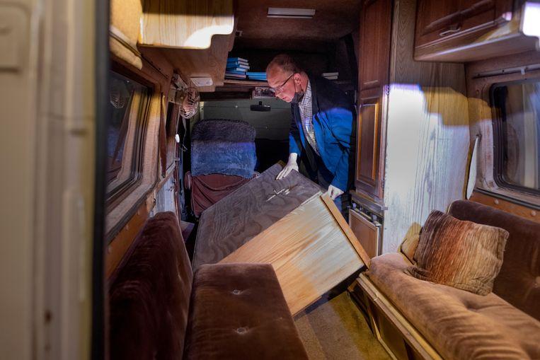 Een medewerker laat in een oude camper zien waar de Bijbels werden verstopt. Beeld Herman Engbers