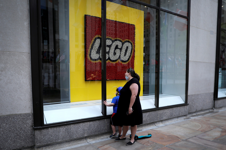 Een vrouw en een kind kijken door het raam van een gesloten Legowinkel in Manhattan, New York. Beeld Reuters
