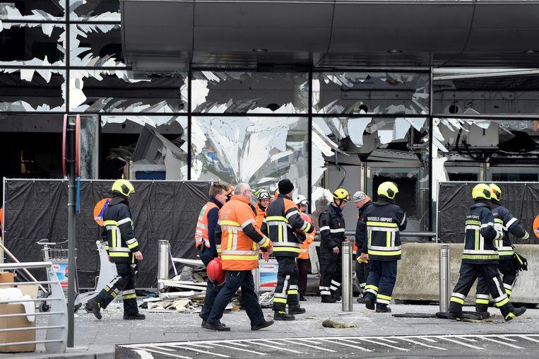 Hulpdiensten bij de beschadigde voorgevel van het vliegveld Zaventem in Brussel, na de bomaanslag op 23 maart 2016. Beeld BELGA