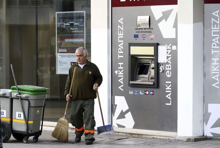 Een schoonmaker veegt nog even de straat in de vroege morgen voordat de banken op Cyprus weer open gaan. Beeld ANP