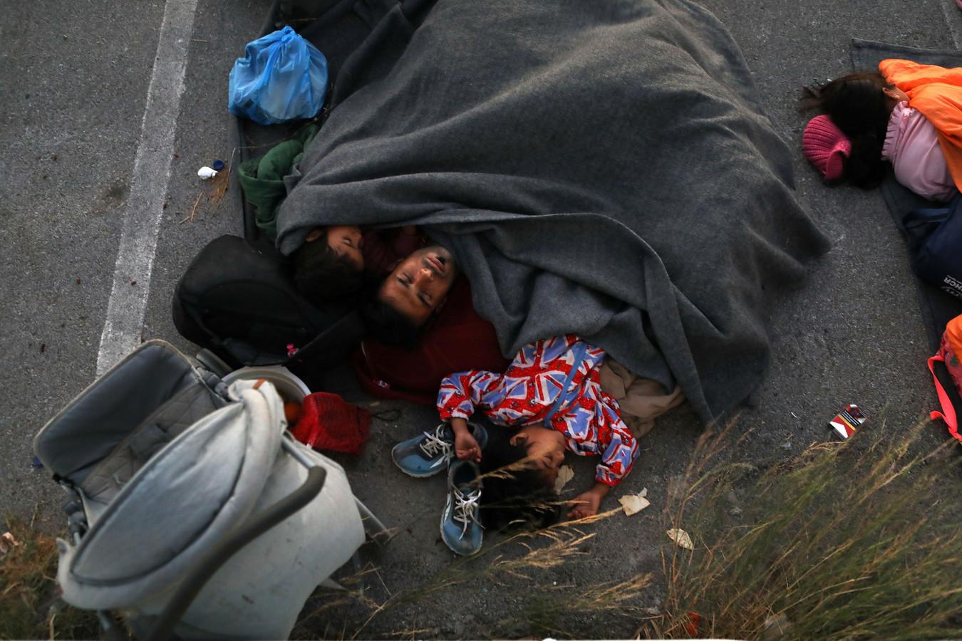 Een familie slaapt noodgedwongen op een parkeerplaats nabij het door brand verwoeste kamp Moria.