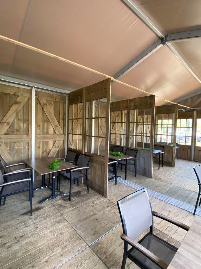 Een derde van het terras is overdekt, met plexiwanden tussen de tafels