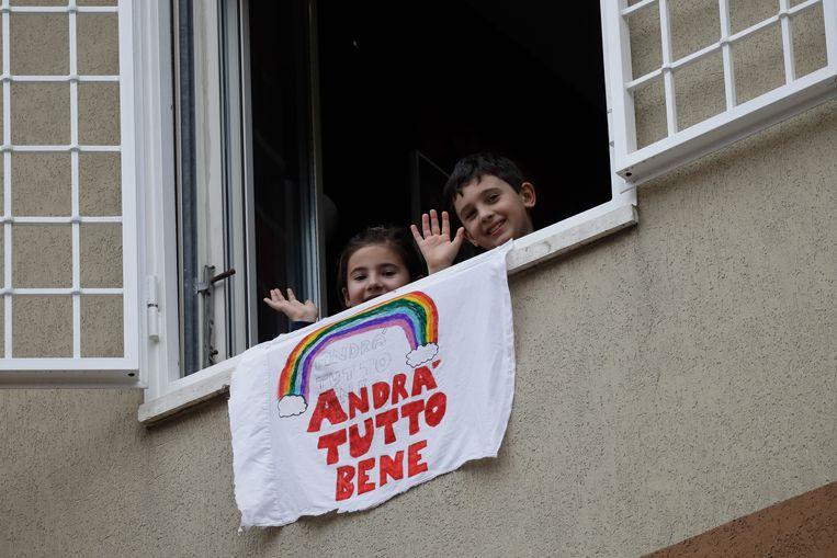 """De kleine Francesco and Greta Innominati zwaaien vanuit hun flat in Rome bij hun zelfgemaakte banner met de tekst """"Alles komt goed'."""