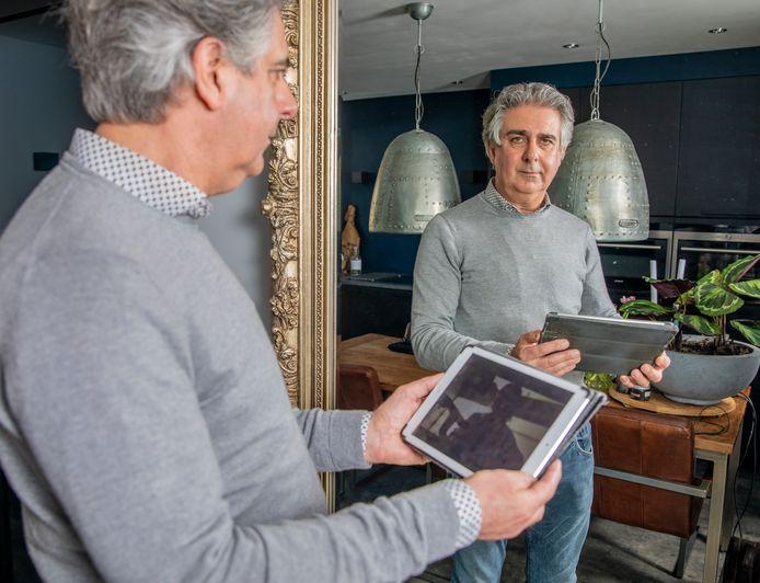Vader Arthur met de tablet waarmee hij contact houdt met zijn dochter.