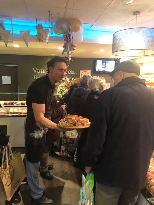 Jeroen van der Steen deelt worstenbroodjes uit in de bakkerij.