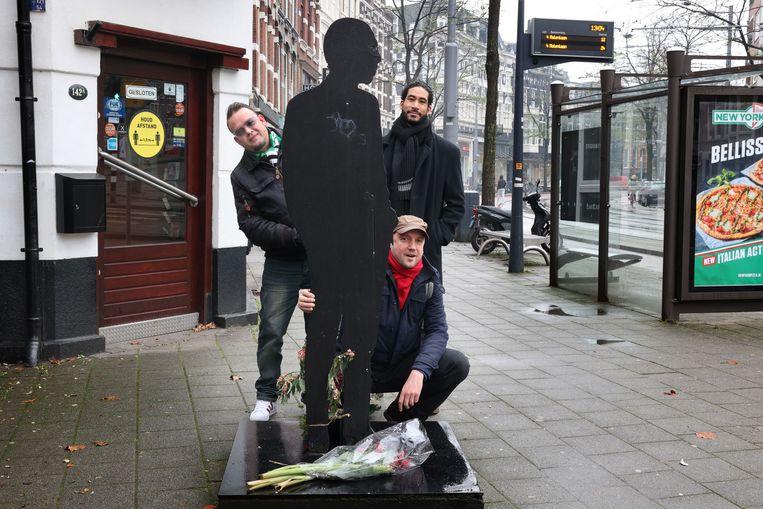 Mark Boninsegna, Miguel Santos en Daniël Dee bij het standbeeld van Jules Deelder op de Nieuwe Binnenweg in Rotterdam.  Beeld Arie Kievit