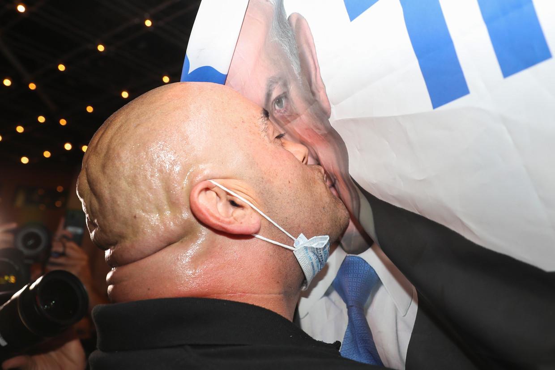 Een aanhanger van premier Benjamin Netanyahu zoent diens beeltenis. Beeld AP
