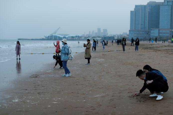 Inwoners van Qingdao genieten van een strandwandeling één dag na het ongeval in de Gele Zee.
