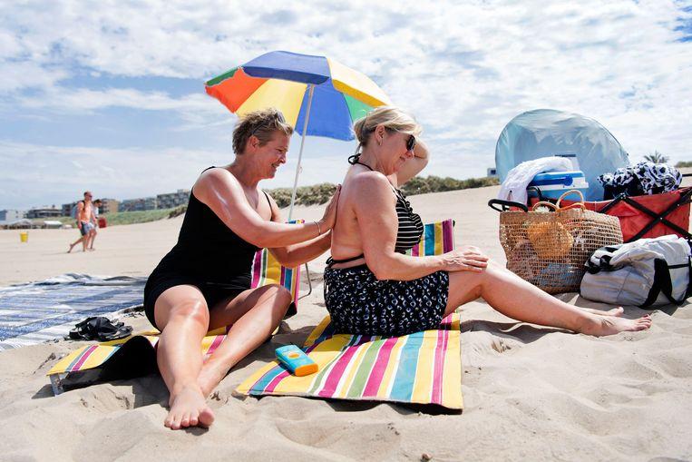 Mirjam Nelissen en Sylvia Gijsberts, hier op het strand van Noordwijk aan Zee, zijn uitgerust met factor 50. Beeld Olaf Kraak