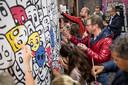 De lange muur in de parkeergarage onder het Kulturhus in Borne. Ketting laat de door hem geschilderde 'gezichtjes' door publiek inkleuren.