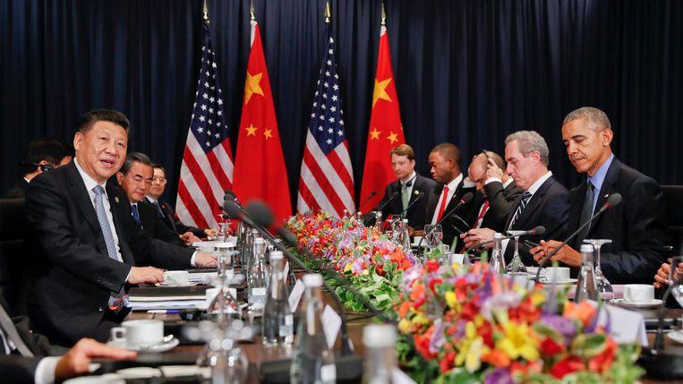 De Chinese president Xi (links) en de Amerikaanse president Obama (rechts) op de APEC-top in Lima.  Beeld AP