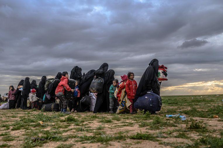 Een stoet van vrouwen en kinderen die wegtrekt uit Baghouz; een foto van Bülent Kiliç die de wereld rondgaat. Beeld AFP