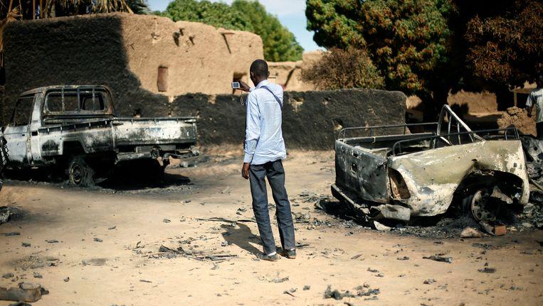 Een man in de Malinese plaats Diabaly maakt een foto van de overblijfselen van een truck die werd gebruikt door radicale moslims. Beeld AP