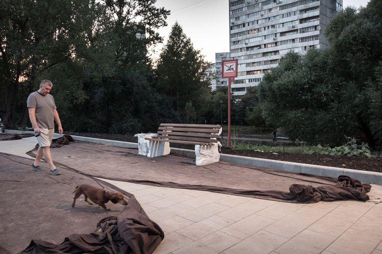Man met hond in de avond aan de Bolshoy Golovinskiy Prud in het Michalkovo Park. Beeld Joel van Houdt