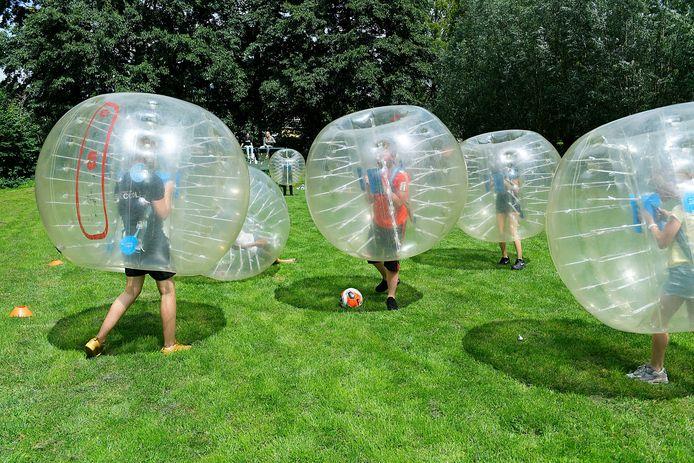 Jongeren spelen bubbelbal op een grasveld. Foto ter illustratie.