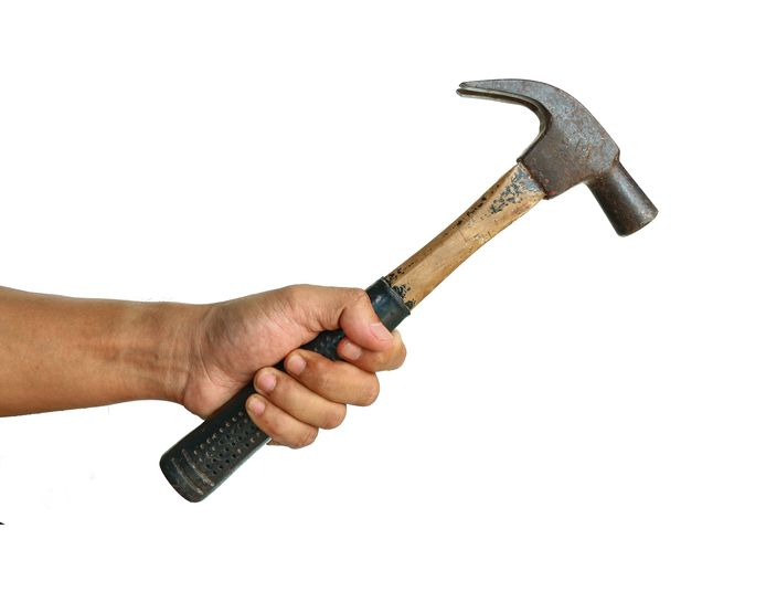 Aggressive human hand holding hammer on white background