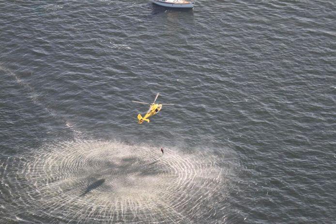 De Kustwacht haalt de zwemster, die kilometers voor de kust van Wassenaar in zee lag, uit het water