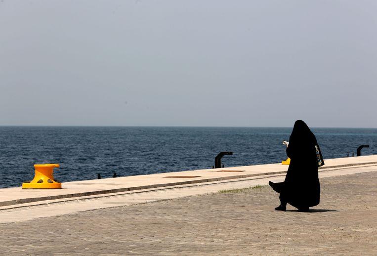 Een gesluierde vrouw loopt langs het water bij de haven van Chabahar.  Beeld AFP