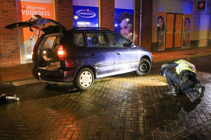 De politie controleert de onderkant van de auto van raadslid Michael Rieter uit Helmond nadat het slachtoffer eronder bevrijd is.
